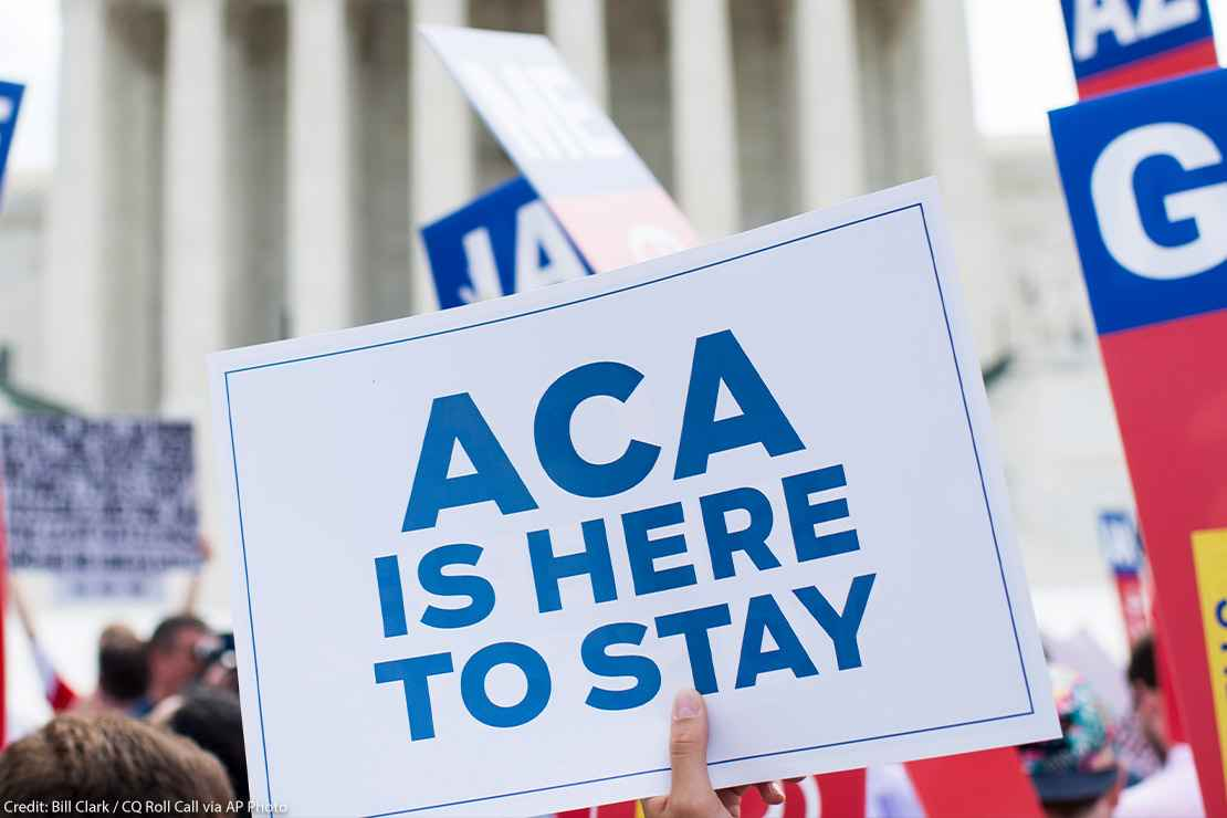 """Affordable Care Act Supporter waves sign that reads """"ACA is here to stay"""" outside of the Supreme Court."""