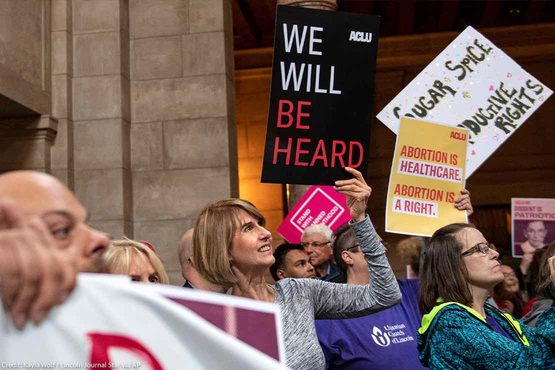 """Supporters of abortion-rights attend a reproductive freedom rally at state capitol in Nebraska, holding ACLU signs that read """"We will be heard"""" and """"abortion is healthcare."""""""
