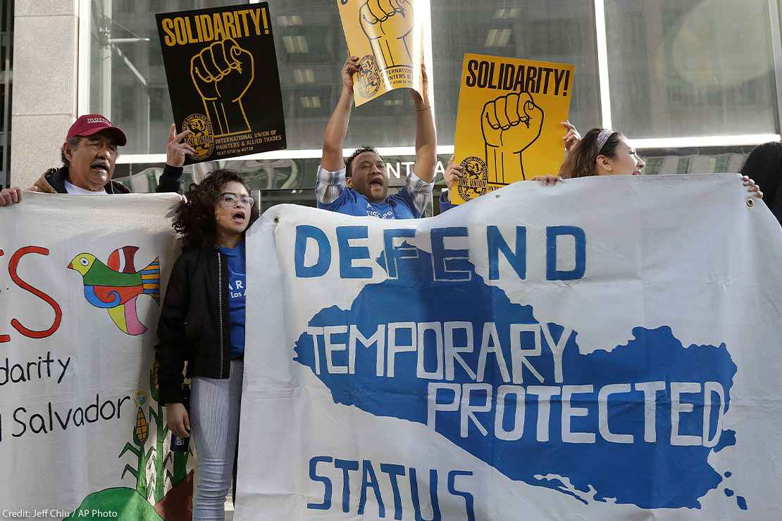 Supporters of temporary protected status immigrants hold signs and cheer at a rally in support of a program that lets immigrants live and work legally in the United States.