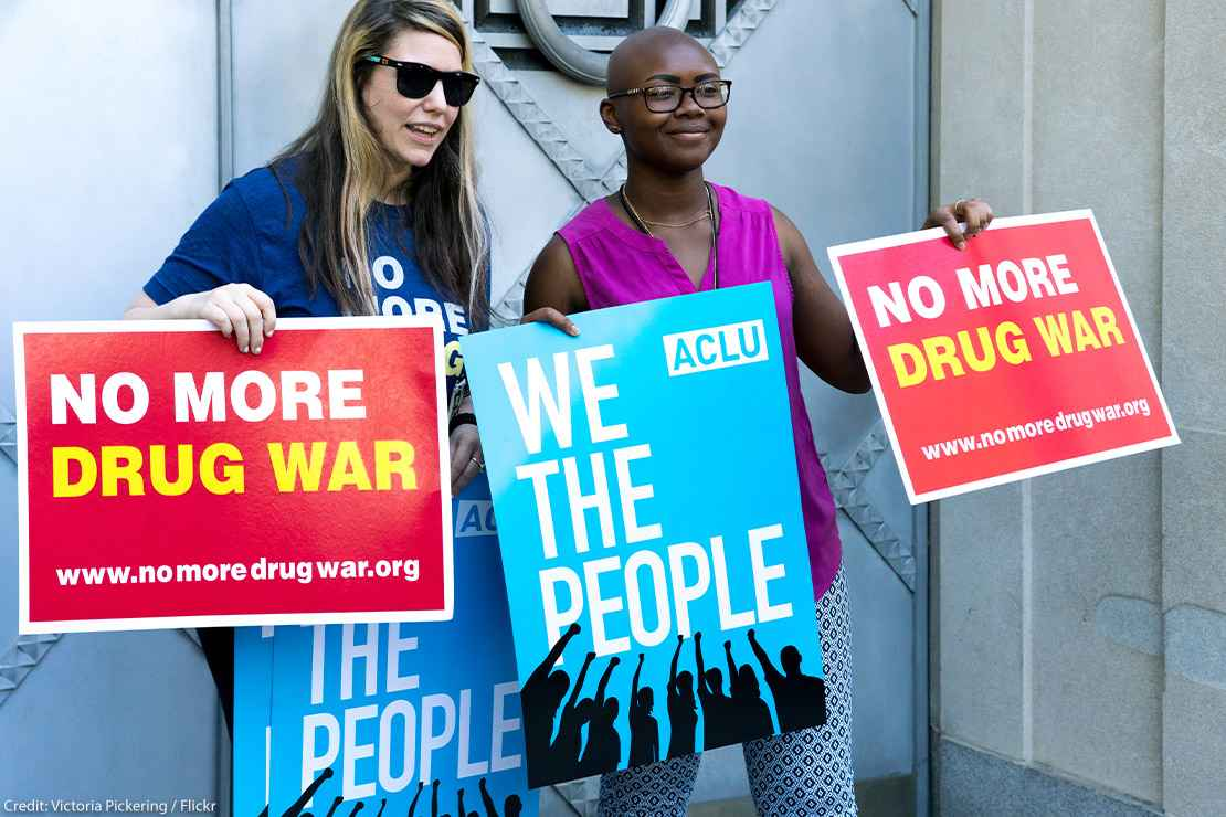 Two protestors holding 'No More Drug War' and ACLU's 'We the People' posters at a protest in front of the Justice Department.