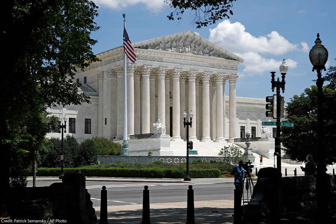 Photo of the American flag on a flag pole and the Supreme Court in Washington, DC.