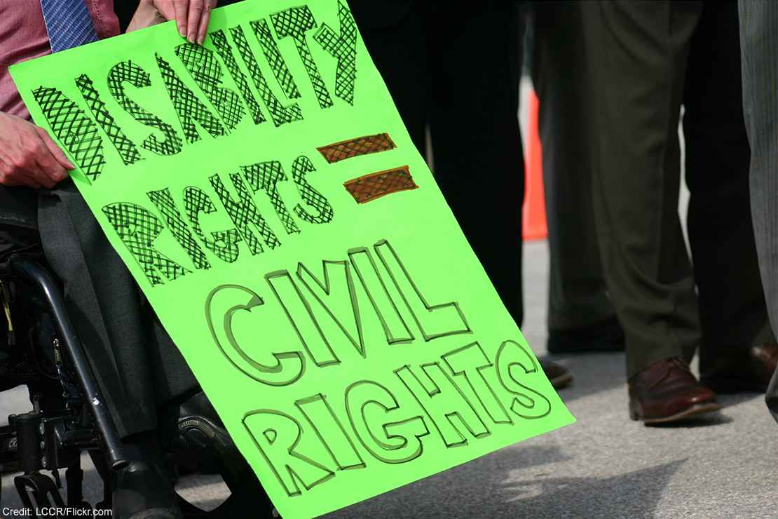 "A wheelchair user holding a sign with the text ""Disability rights = civil rights."""