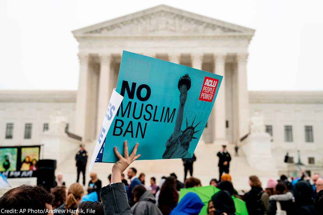 "In this April 25, 2018 file photo, a person holds up a sign that reads ""No Muslim Ban"" during an anti-Muslim ban rally in front of the Supreme Court building in Washington, DC."